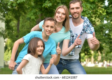 family posing  with thumbs up