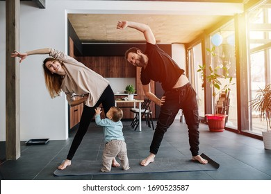 The family practices yoga, family life in isolation. Mom and dad are doing exercises, and infant child creeps next to his parents. Sunset light from the windows. Family quarantine