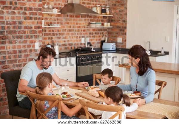 Famille Priant Avant De Manger Dans La Cuisine Ensemble