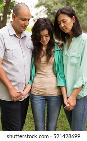 Family praying with their daughter.