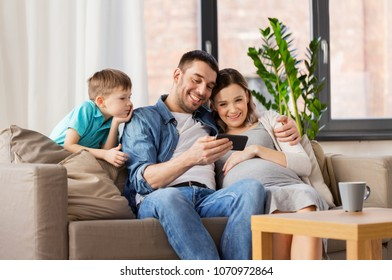 family, pregnancy and technology concept - happy pregnant mother, father and little son with smartphone sitting on on sofa at home
