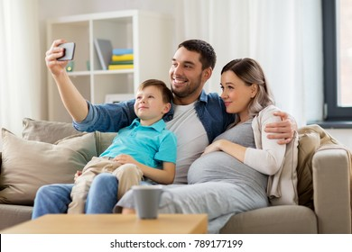 family, pregnancy and technology concept - happy pregnant mother, father and little son taking selfie with smartphone sitting on on sofa at home