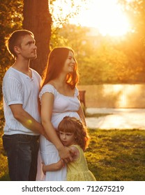 Family. Pregnant mother, father and daughter. Father hugs mother, and mother and daughter hug each other. Family portrait at sunset. Happiness of parenthood