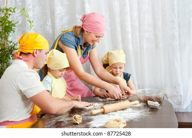 The family is preparing dough, Mom keeps the pan with the rolls