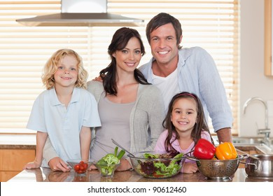 Family preparing a salad together in a kitchen