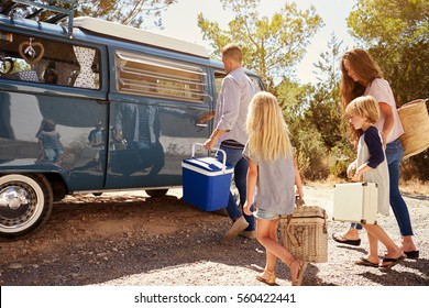 Family preparing their camper van for a road trip, side view