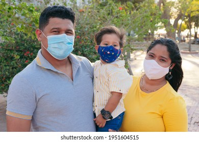 Family with protective mask holding baby in park