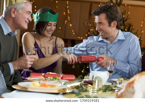 Family pulling Christmas confetti crackers