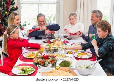 Family pulling christmas crackers at the dinner table at home in the living room
