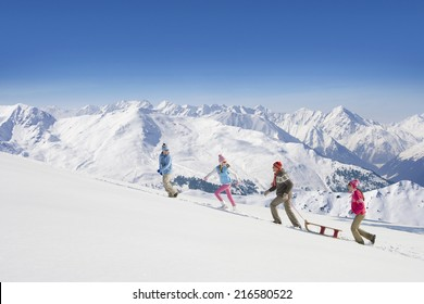 Family pulling sled uphill with mountains in background