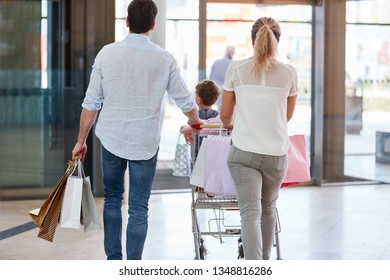 Family pushes their shopping in the shopping cart to the exit in the mall