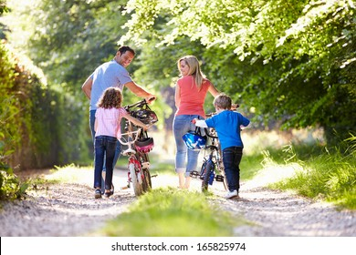 Family Pushing Bikes Along Country Track