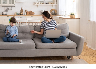 Family, quarantine, distance job concept. Mother freelancer remote work from home office on laptop during lockdown sitting on couch, kid shows digital tablet to busy mom, distracts, asks for attention