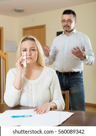 Family quarrel over financial documents at home. Focus on girl