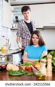 Family quarrel. Sad woman listening to man at home kitchen