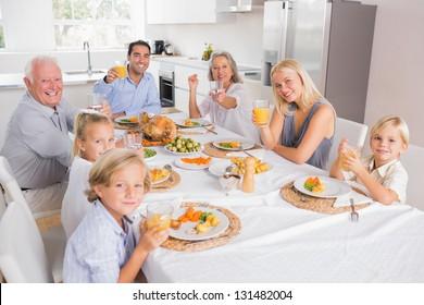 Family raising their glasses at thanksgiving and looking at camera
