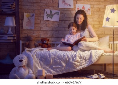 Family reading bedtime. Pretty young mother reading a book to her daughter. Happy time at home.