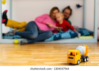 Family reading book at children room with plastic truck toy on first plan.