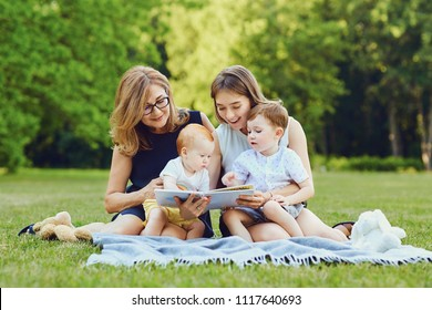 A family is reading a book on the grass.