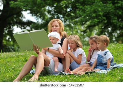 Family reading a book outdoors in the park