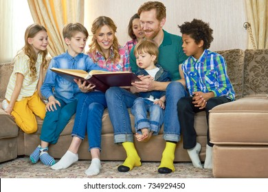 Family reading a book. People sitting on the sofa.