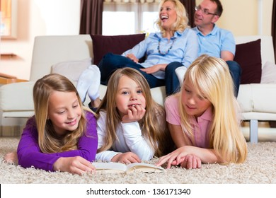 Family reading a book together at home in their living room
