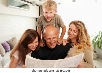 Family reads the newspaper at home