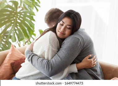 Family Reconciliation. Loving Spouses Hugging After Effective Couple Therapy Sitting In Psychologist's Office