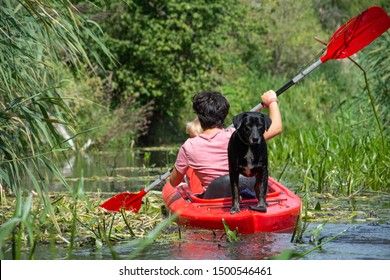 Family in a red kayak, rafting on the river - dog in a kayak