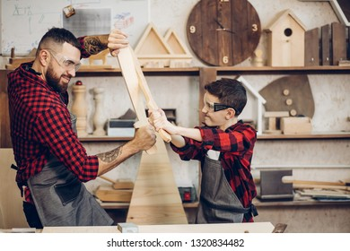Family relations, fatherhood, hobby, carpentry, woodwork concept - Father and son playing knights with wooden DIY swords at carpenter workshop