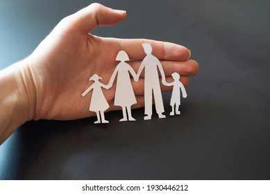 family and relationships concept - closeup of woman cupped hands showing paper man family. happy family concept.