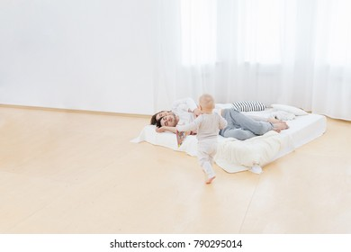 Family and relationships concept. Little one-years old baby boy spend time alone while his parents sleep tight after playing with child. Funny lifestyle family photo