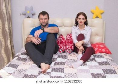 family relationships. Family problems - a portrait of the father and daughter in a family conflict in the room. They sit right in front of the camera and look unhappy