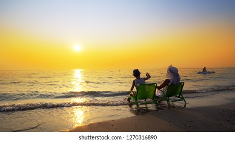 Family relax playing with sand sitting on beach chair in vacations with sunset and blue sky background