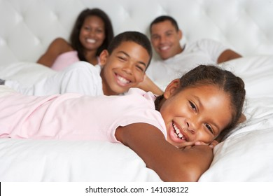 Family Relaxing In Bed Together