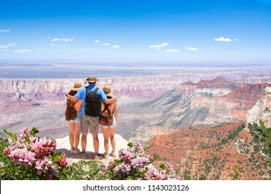 Family relaxing and enjoying beautiful mountain view  on vacation hiking trip. Father with arms around his family. North Rim. Grand Canyon National Park, Arizona, USA.