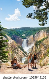 Family relaxing and enjoying beautiful view of waterfall on hiking trip in the mountains.  Beautiful Lower Falls at Yellowstone National Park, U.S.A.