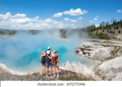 Family relaxing and enjoying beautiful view of gazer on vacation hiking trip. Father with arms around his family. Excelsior Geyser from the Midway Basin in Yellowstone National Park. Wyoming, USA