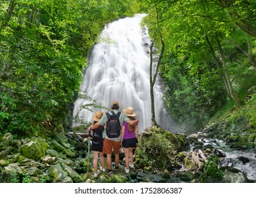 Family relaxing and enjoying beautiful view on vacation hiking trip. Father with arms around his family looking at waterfall.  Crabtree Falls just off the Blue Ridge Parkway. North Carolina,