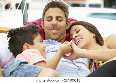 Family Relaxing In Garden Hammock Together