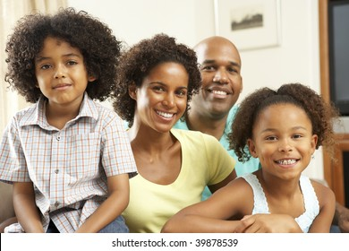 Family Relaxing At Home On Sofa