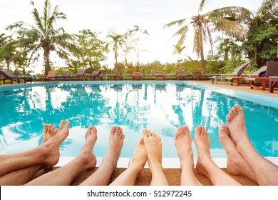 family relaxing near swimming pool in hotel, feet of group of friends or parents with children, happy beach holidays