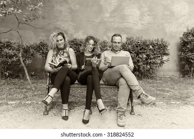 Family relaxing on a park bench.