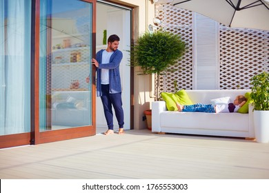 family relaxing on the patio at summer day, man opens sliding doors