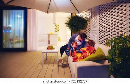 family relaxing on patio zone with open space kitchen and sliding doors on background