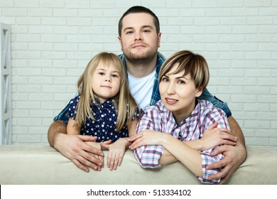 Family relaxing on sofa at home. The family father, mother and happy daughter sitting on the sofa hugging and looking at the camera.