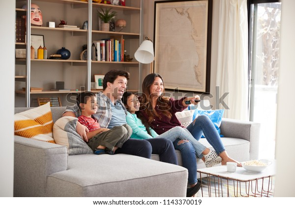Family Relaxing On Sofa At Home Watching Television