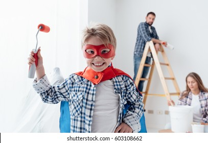 Family renovating their home and painting walls, the boy is wearing a superhero costume and holding a paint roller
