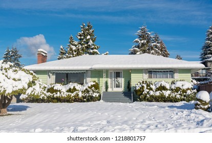 Family residential house with front yard in snow. North American house on winter sunny day