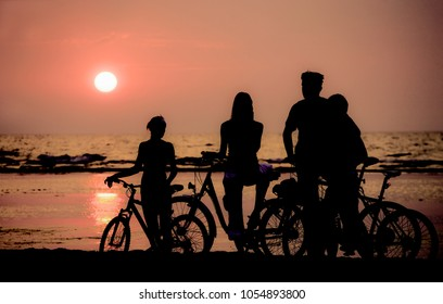 Family rest on bicycles. Sunset. Contours.